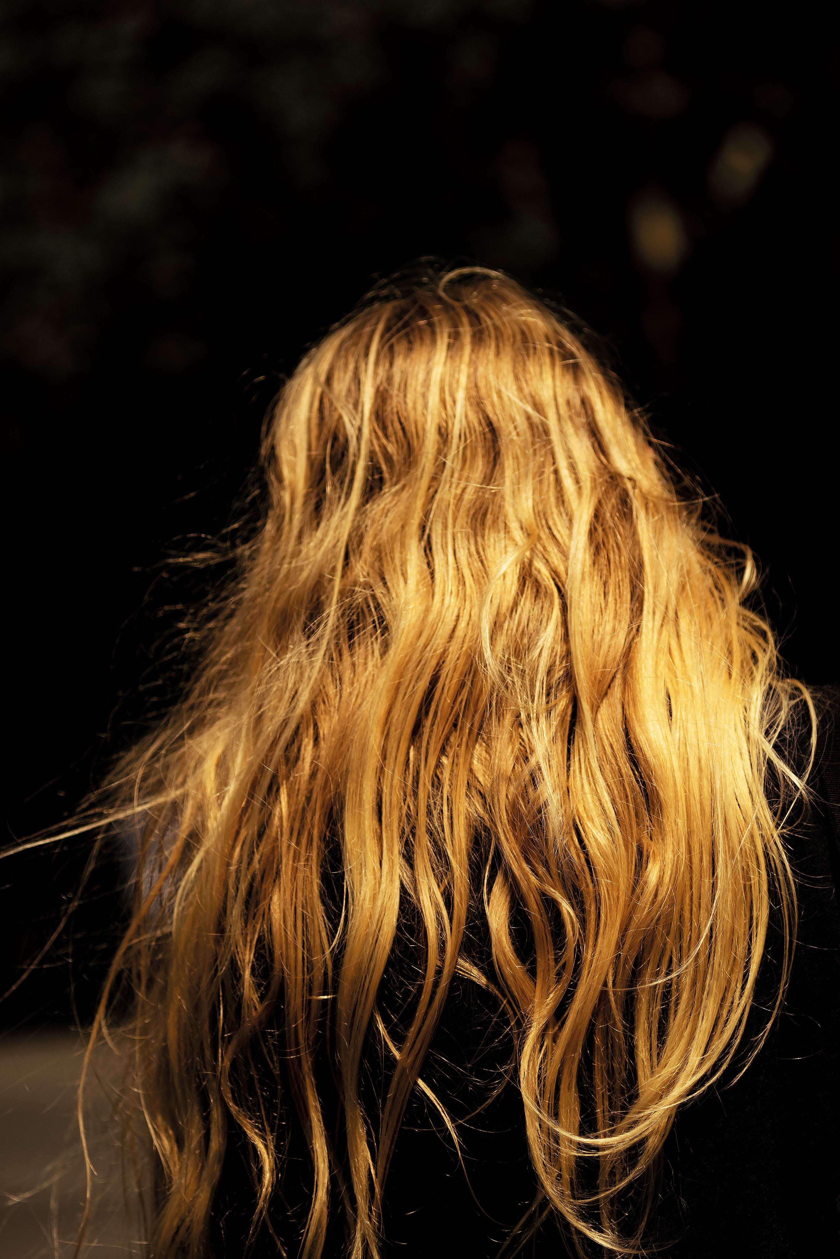 the back of a red headed woman with long curly hair, dark background