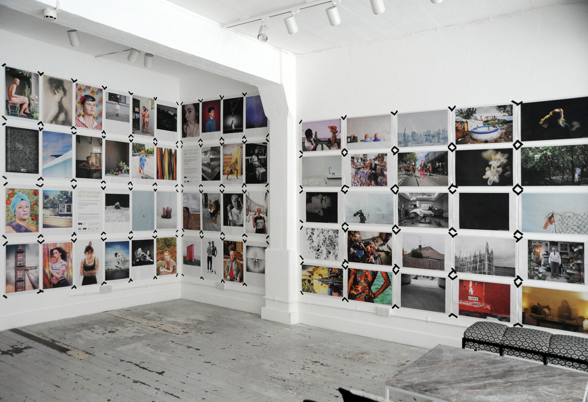 Shutter Hub OPEN exhibition 2018 - gallery space in the Old Truman Brewery, walls covered with newsprint photographs taped to the walls