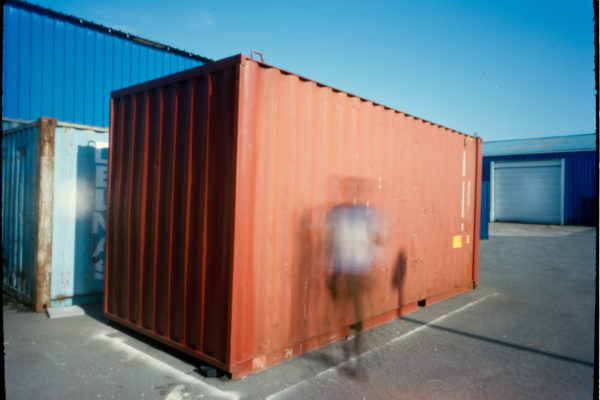 This is an out of focus refugee photographed in front of a red container.