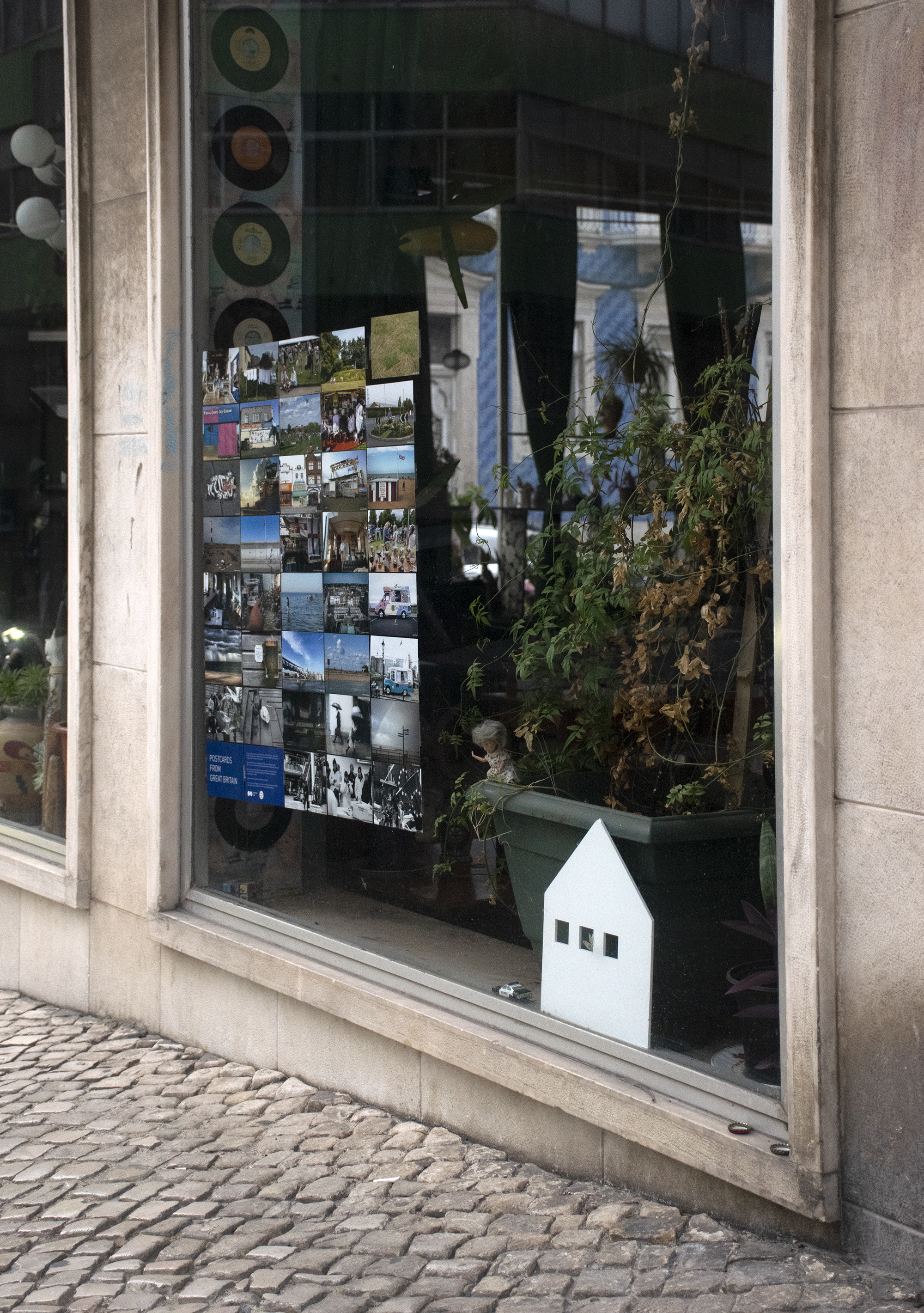 A street in Lisbon, Portugal. In one of the shop windows there is an exhibition of Shutter Hubs Postcards from Great Britain project, lots of postcard sized photographs