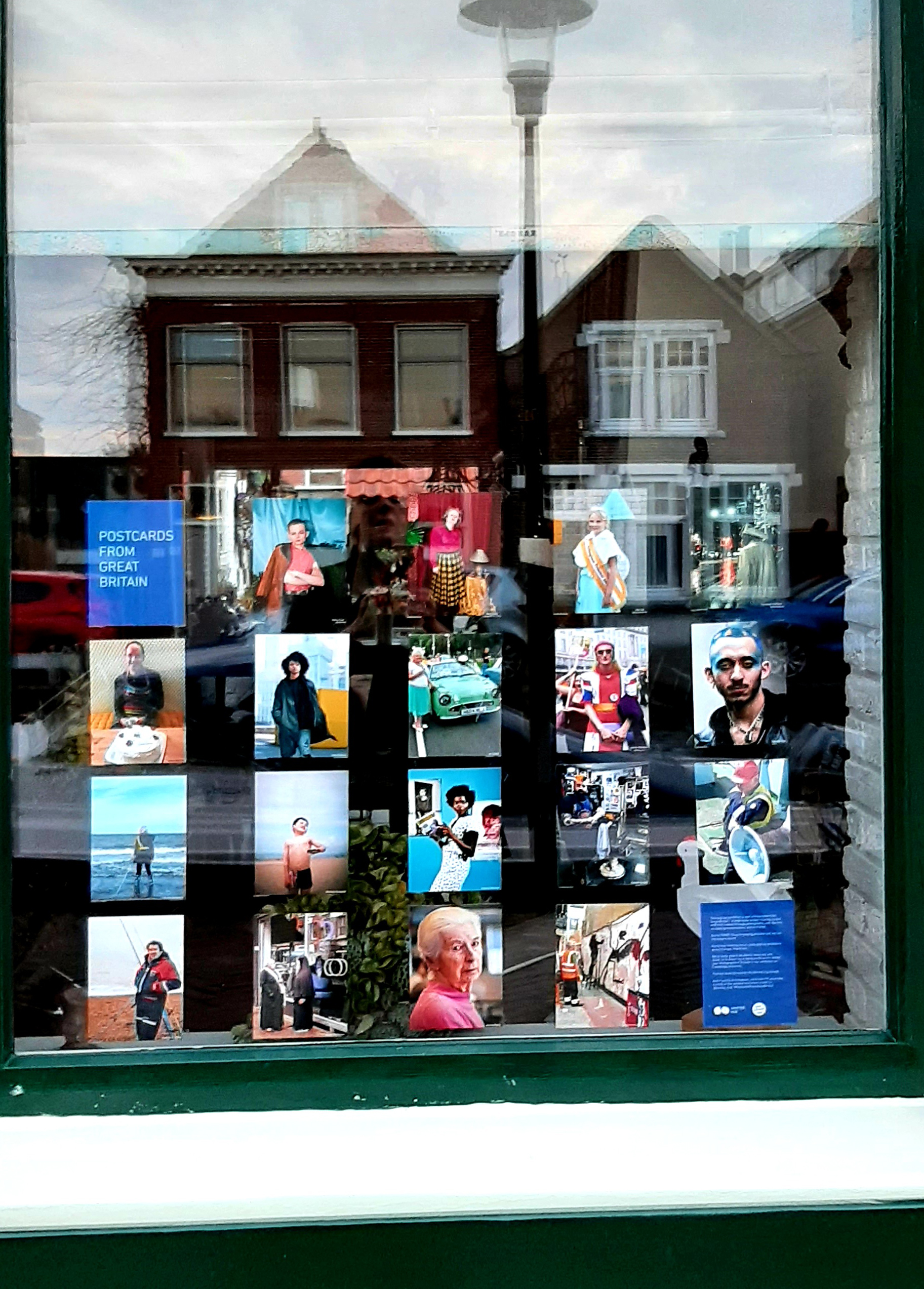 Photograph of a window displaying postcard-sized photographs, with buildings reflected in the top of the window.