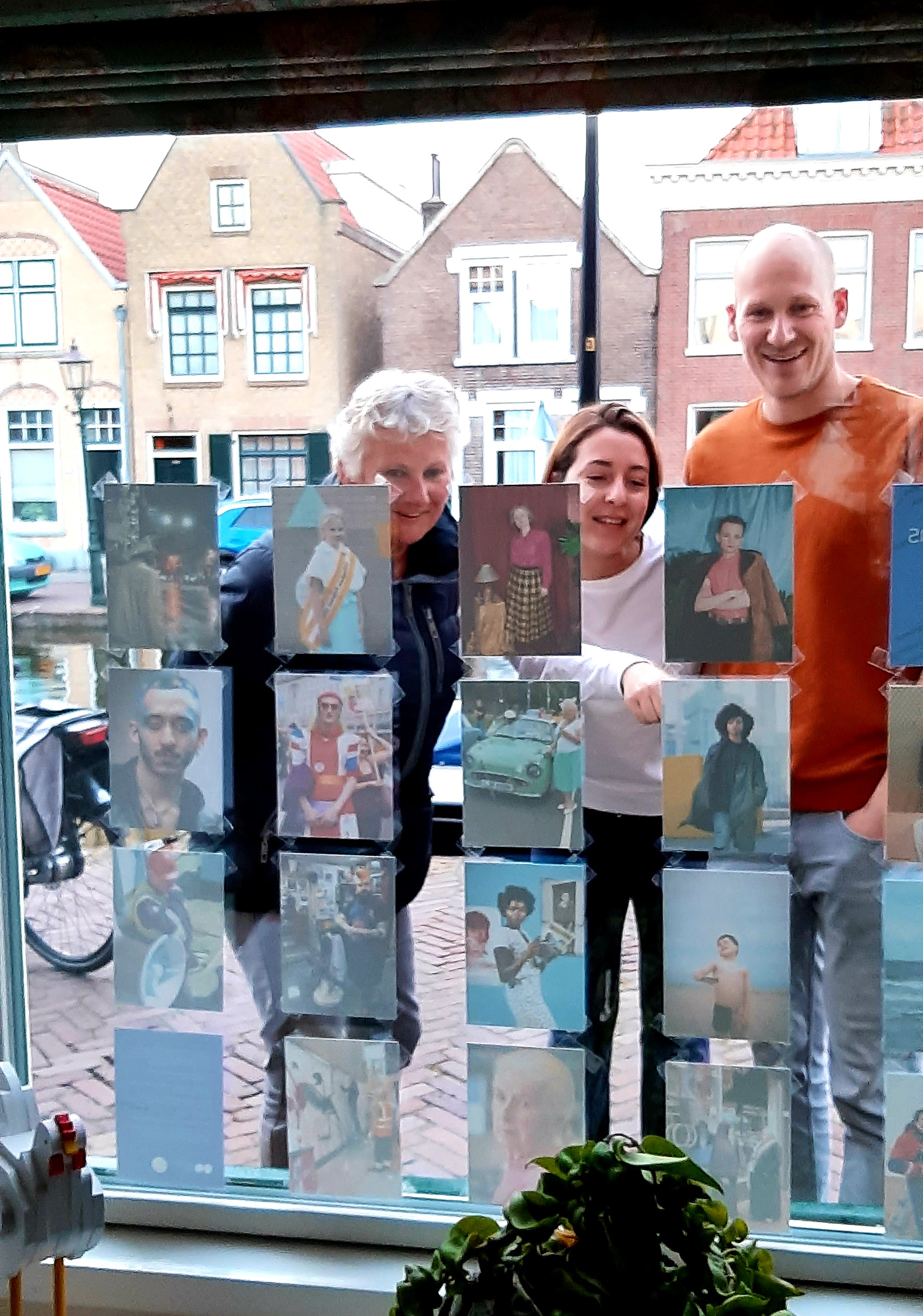 Photograph looking out of a window displaying postcard-sized photographs, with three people looking at the images and smiling, with buildings behind them in the background.