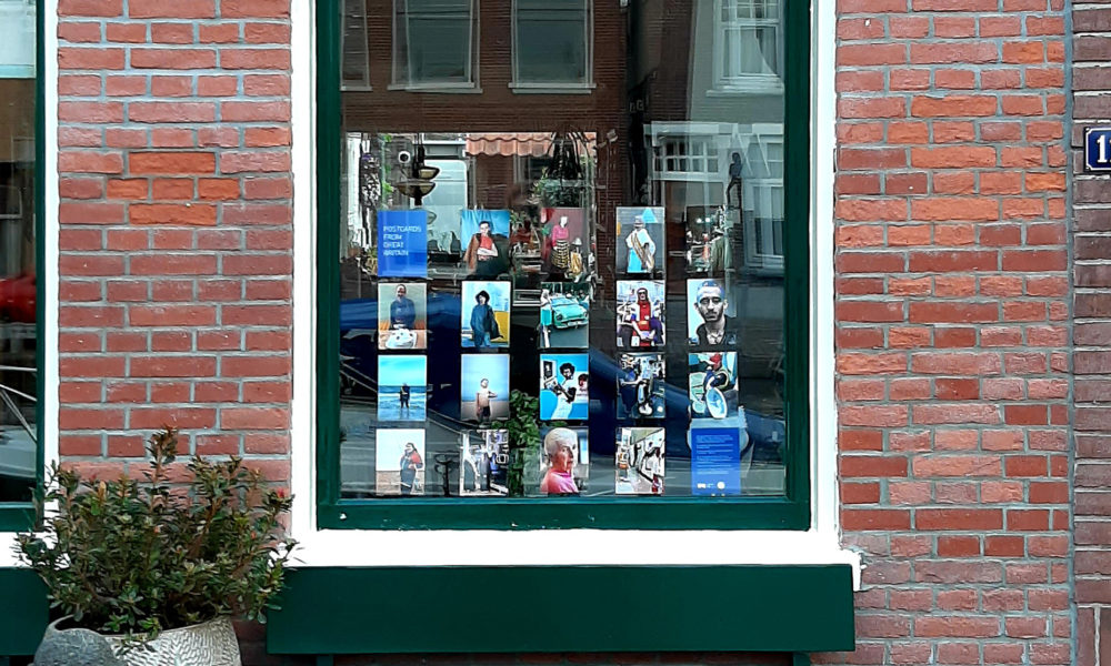 Photograph of a window displaying postcard-sized photographs, with brick wall either side, a green wooden bench in front and a potted plant to the left.