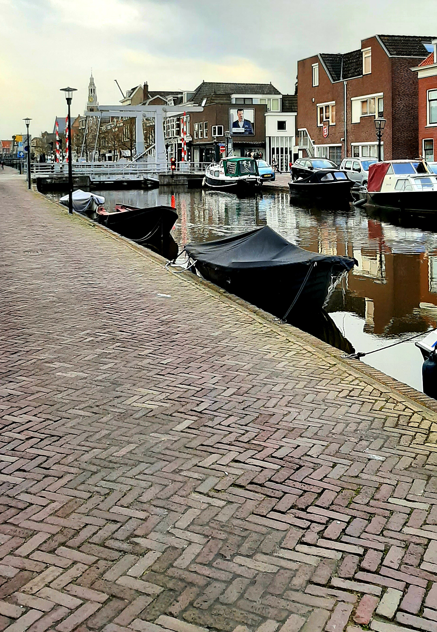 Photograph showing a canal with boats (some covered in protective fabric), buildings in the distance and a brick footpath in the foreground