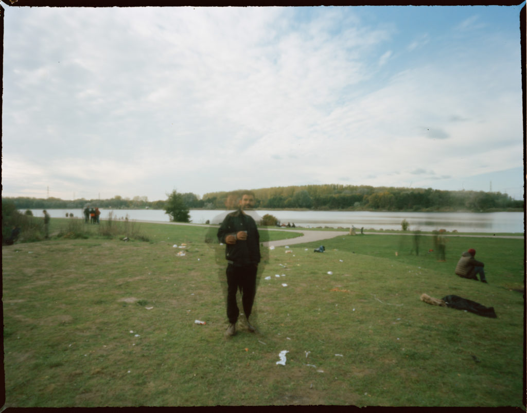 A refugee who is out of focus photographed with a campsite's lake in the background.