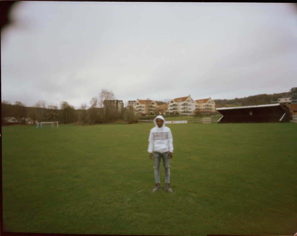 An out of focus refugee photographed in a green field but the weather is overcast and cold.