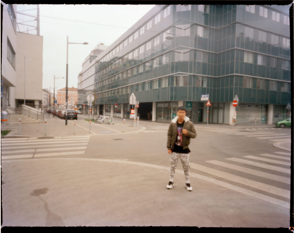 A male out of focus refugee is photographed outside a modern building that is the central police station in Vienna.