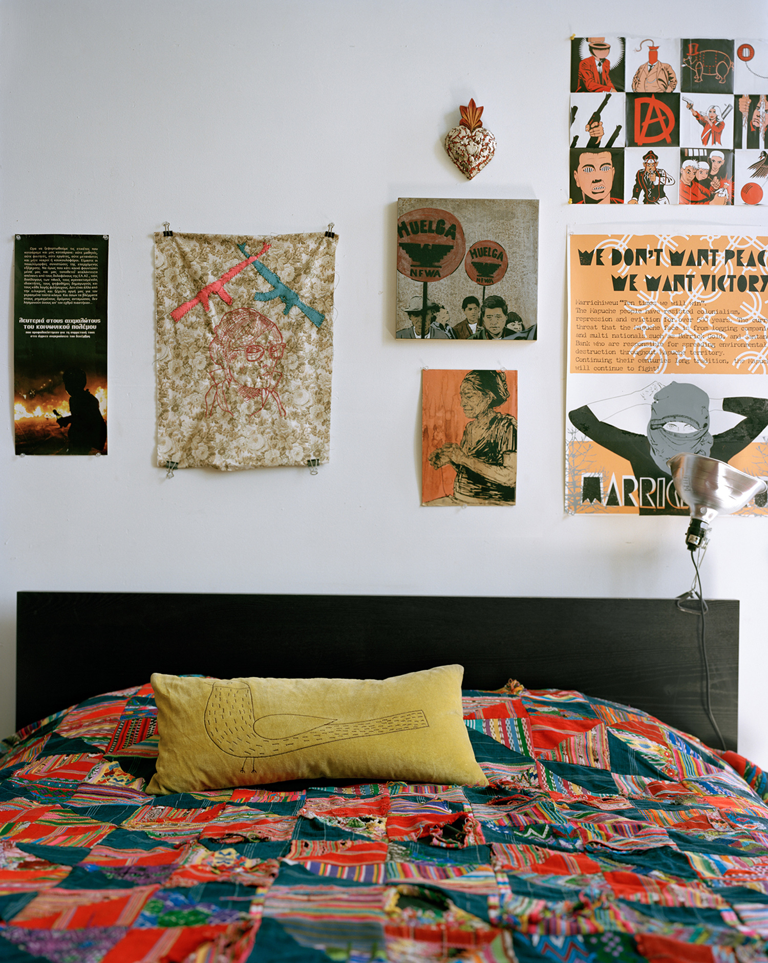 Close up of a bed with a colourful cover against a wall filled with posters, artworks and drawings.