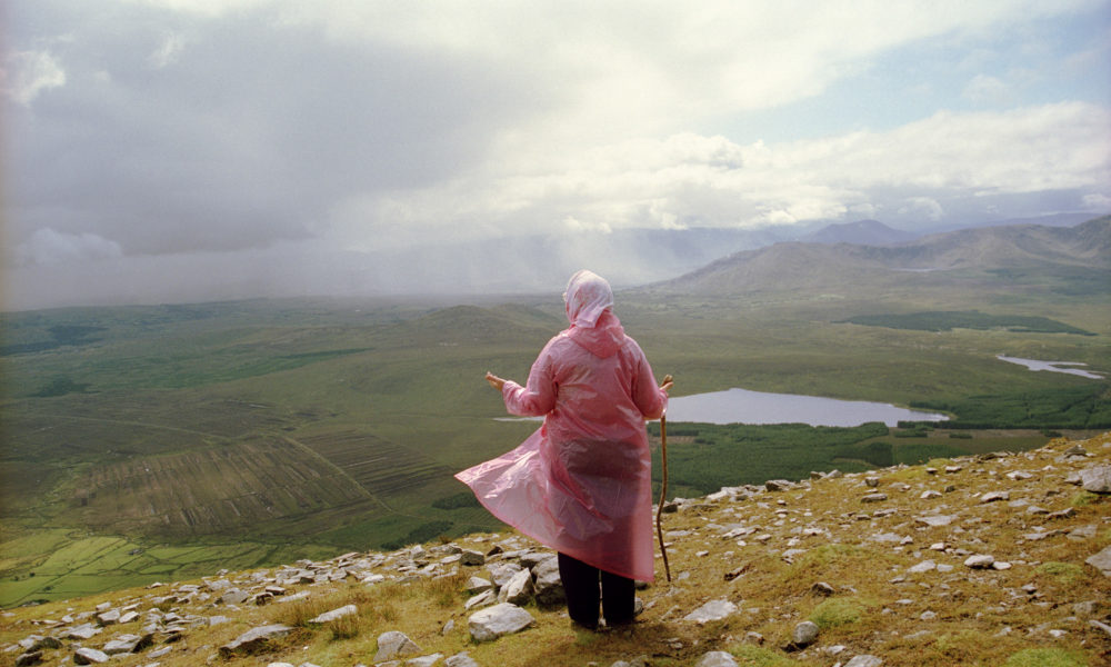 Photograph of a woman in a pink rain coat looking at the view from a hill/mountain with a lake in the distance