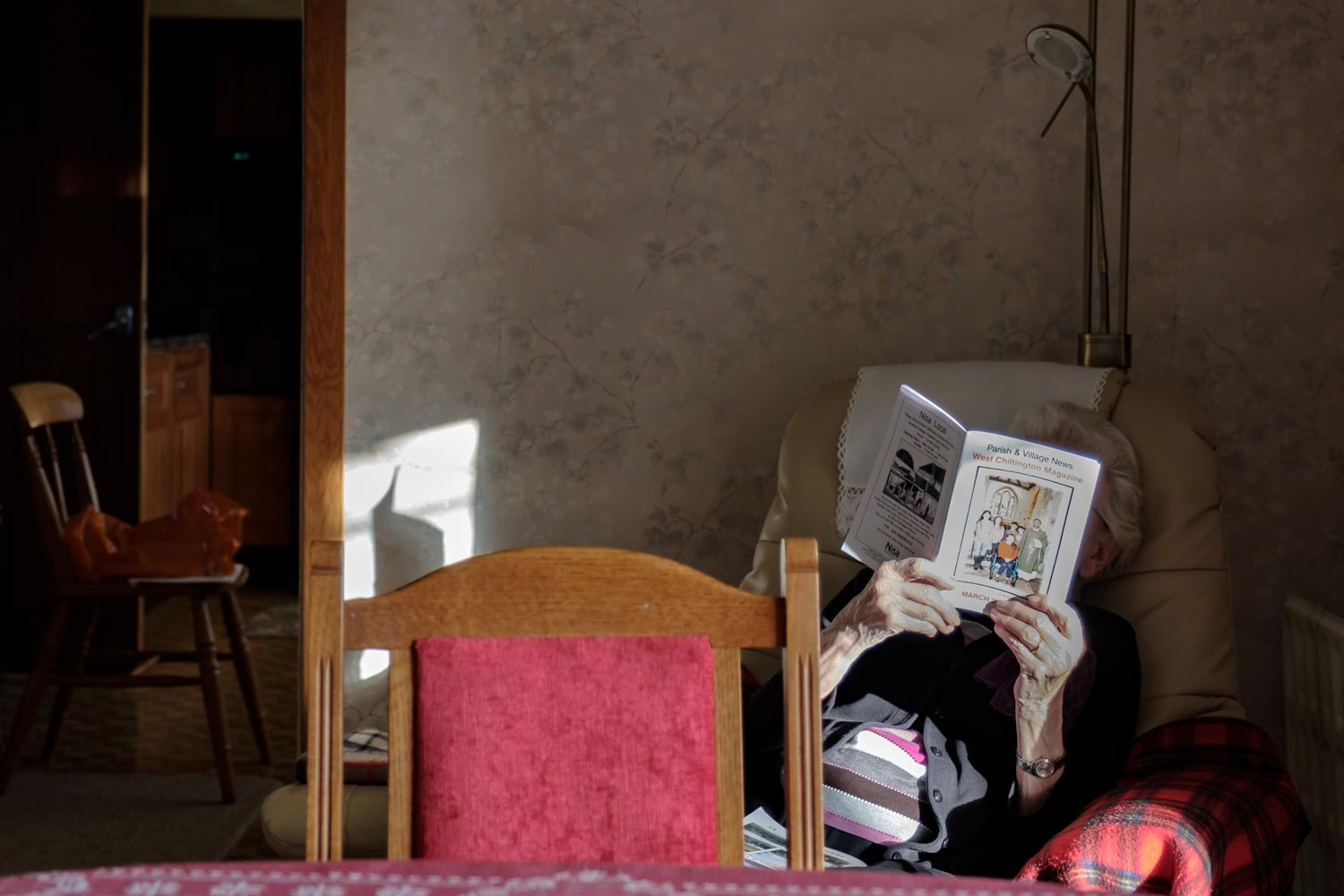 Older woman sitting in a chair with a book covering her face in the corner of living room.