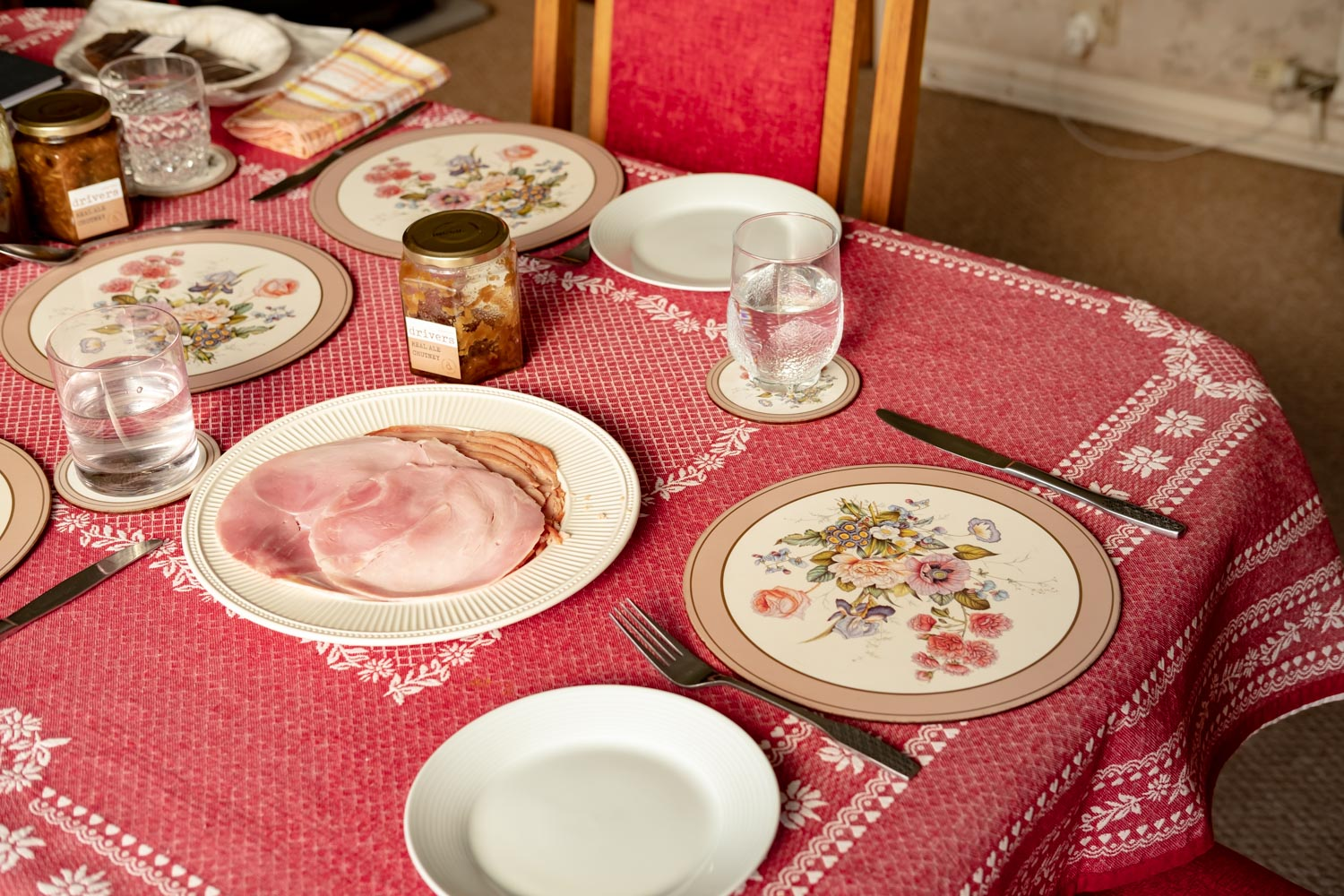 Table set with a red table cloth and placemats. On the middle of the table is a plate of sliced ham and a jar of chutney waiting to be eaten.