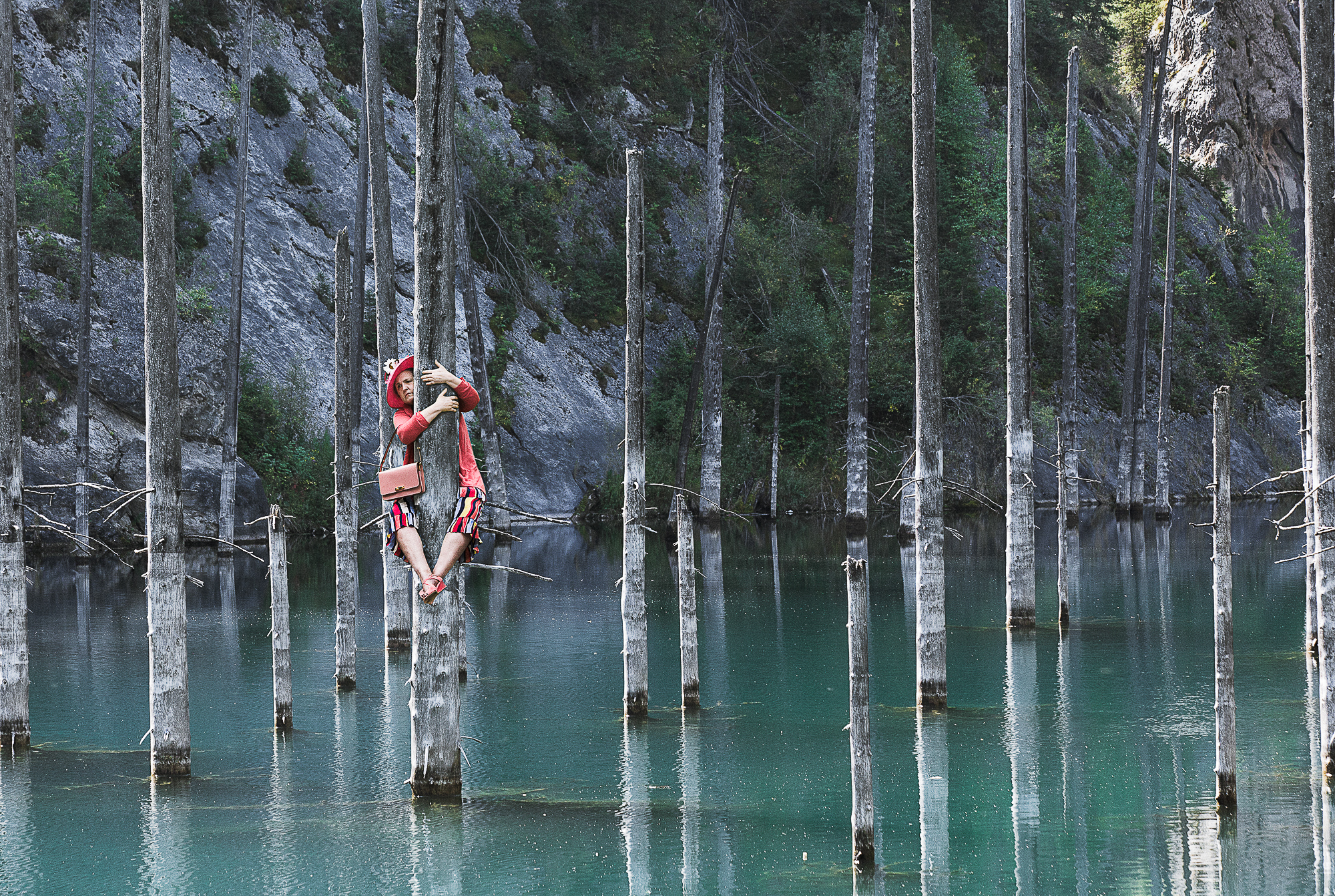 Photograph of a woman dressed for a garden party clings to a dead tree in the middle of a lake