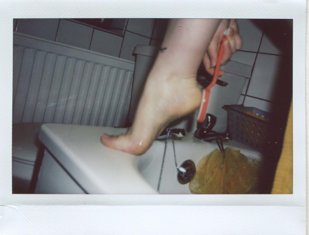 Instax wide print showing the artist's foot on the corner of the bath in the middle of the frame. She is holding a foot file to her heel.