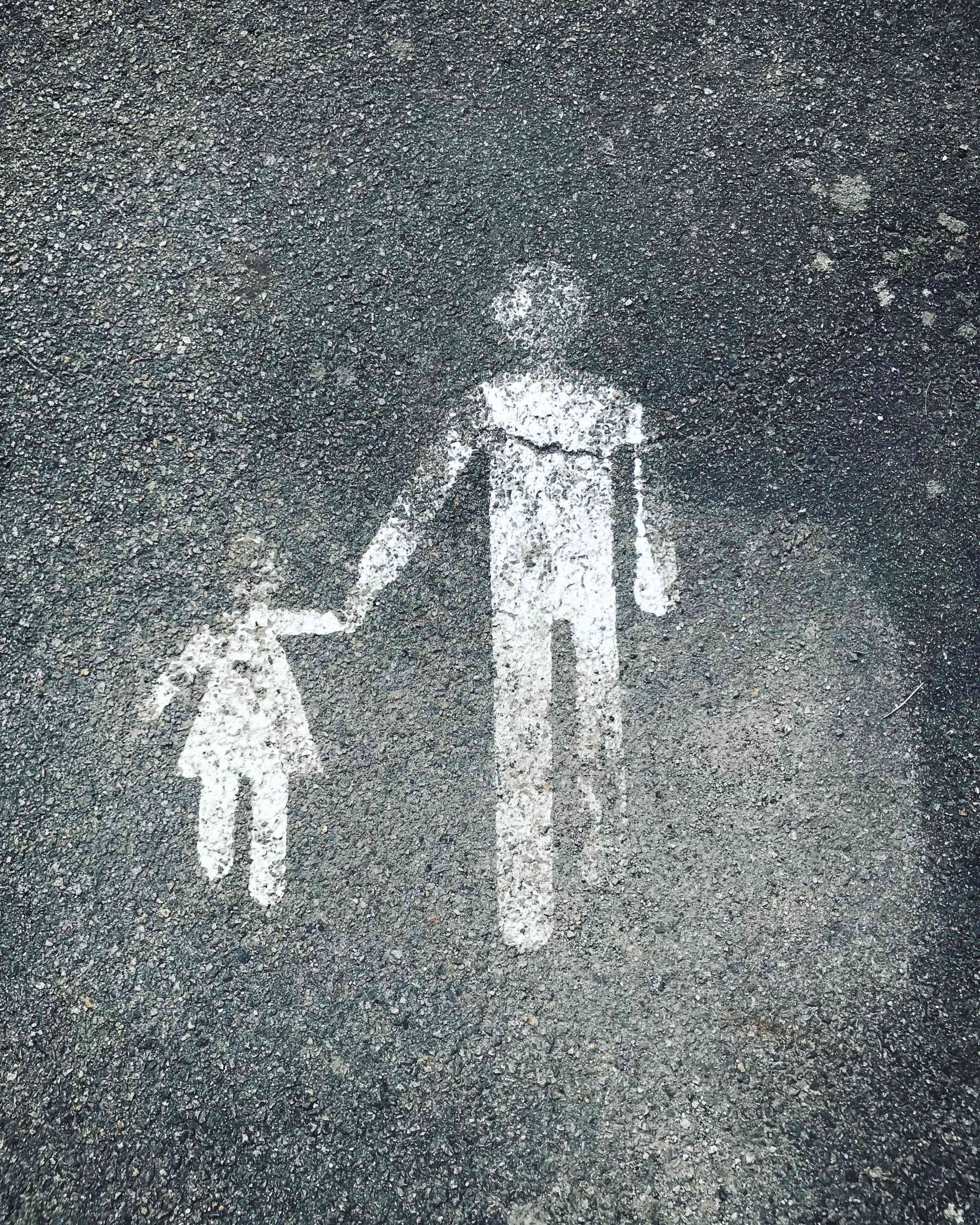 Photograph of a floor surface painted with a white graphic of a small person in a dress holding hands with a taller person in trousers