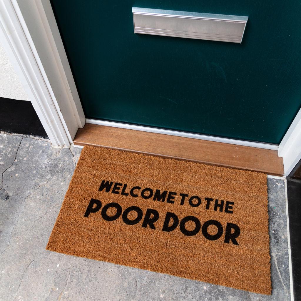 Photograph of a door mat outside a flat door with welcome to the poor door printed on it.