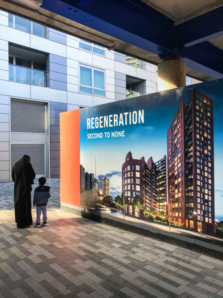 Photograph of mother and child next to luxury development hoarding saying regeneration second to none.