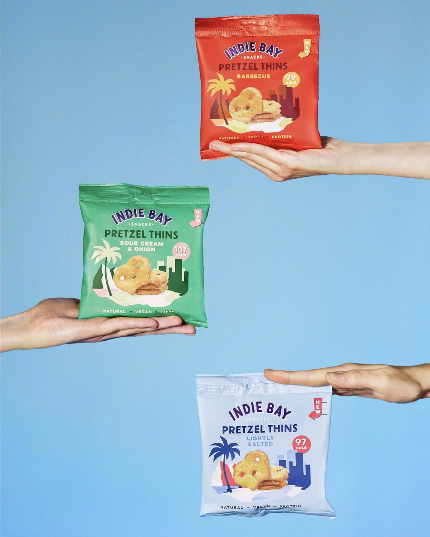 3 hands holding bags of pretzels