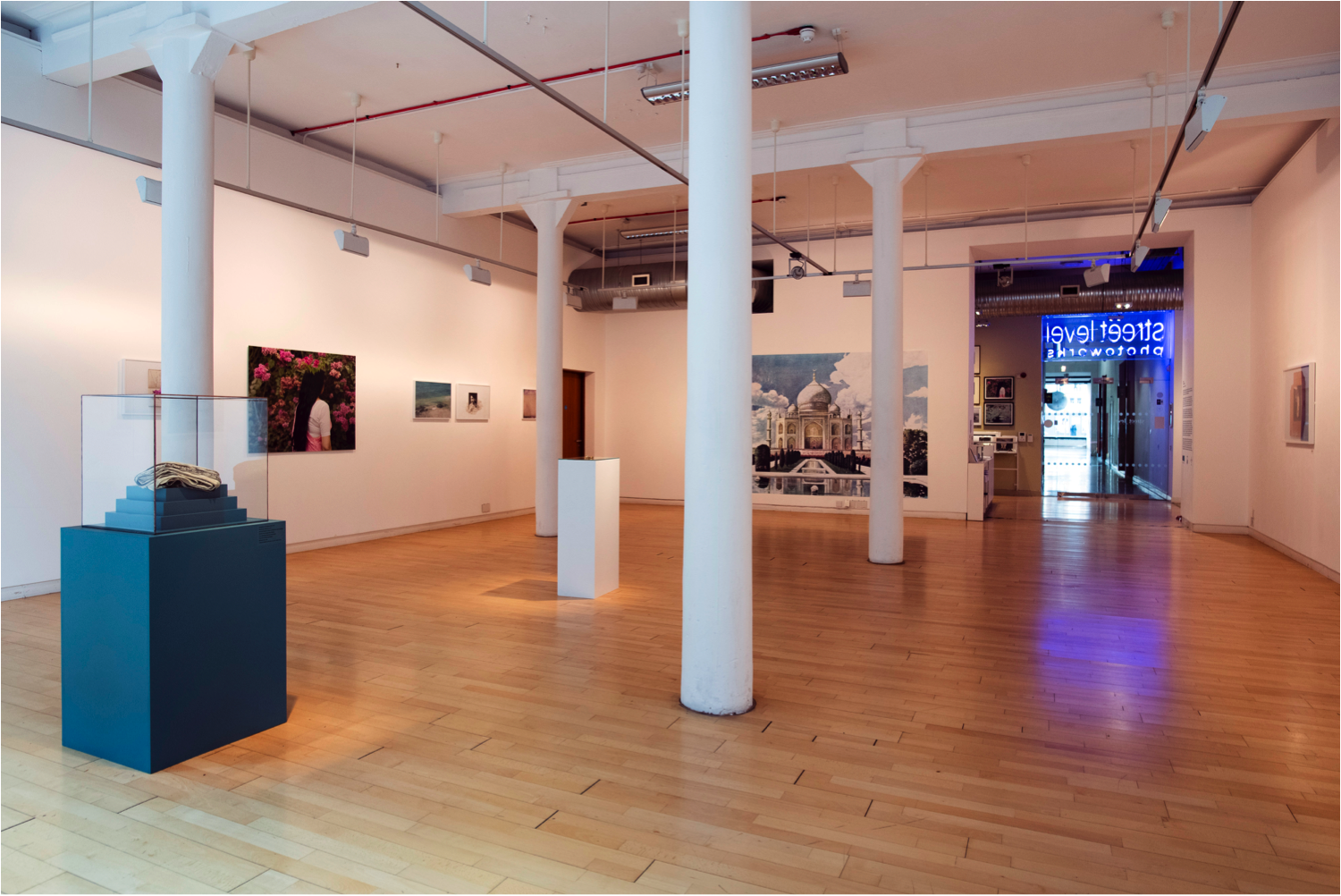 Photograph showing the interior of Street Level Photoworks gallery, with photographs displayed on the wall and an object in a display case with a blue plinth to the left. A neon sign reading 'Street Level Photoworks' can be seen in the doorway to the right, viewed from behind so as if mirrored.