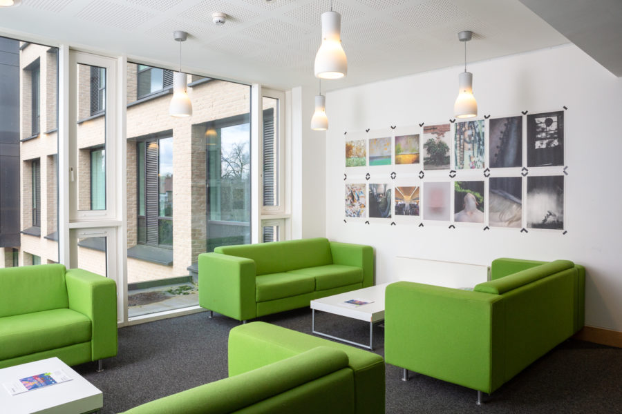 Photograph of a seating area with green sofas in Art at the ARB at University of Cambridge, with poster prints displayed on the wall and exterior windows visible through the large window to the left