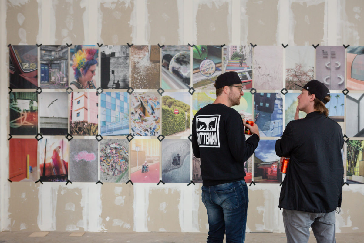 Two people having a discussion in front of the Shutter Hub STREET / FORM exhibition at POW! WOW! Rotterdam, showing a wall in an empty shop premises with newsprint images taped to the wall