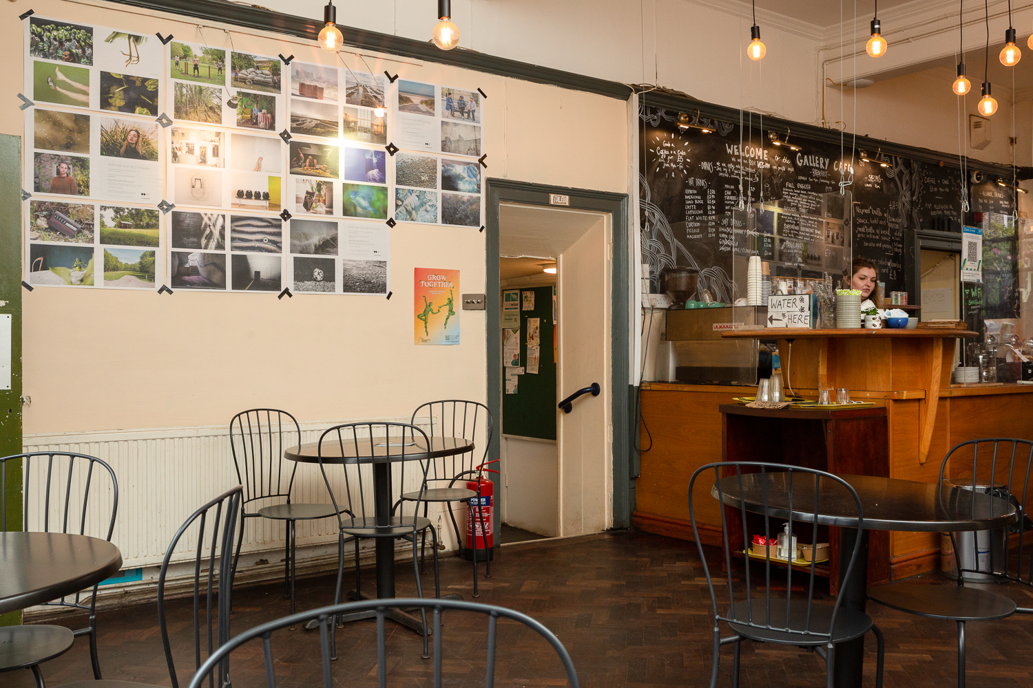 Photograph in the Gallery Café at St. Margaret's House, showing an exhibition of photographs printed on newsprint, tables and chairs in the foreground, and the café counter to the right.