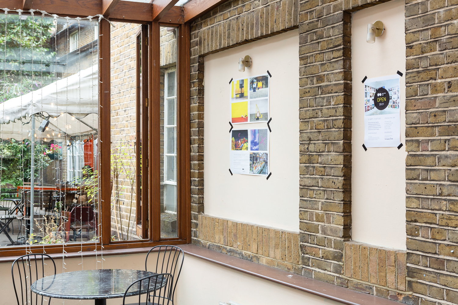 Photograph in the Gallery Café at St. Margaret's House, showing an exhibition of photographs printed on newsprint, tables and chairs in the foreground