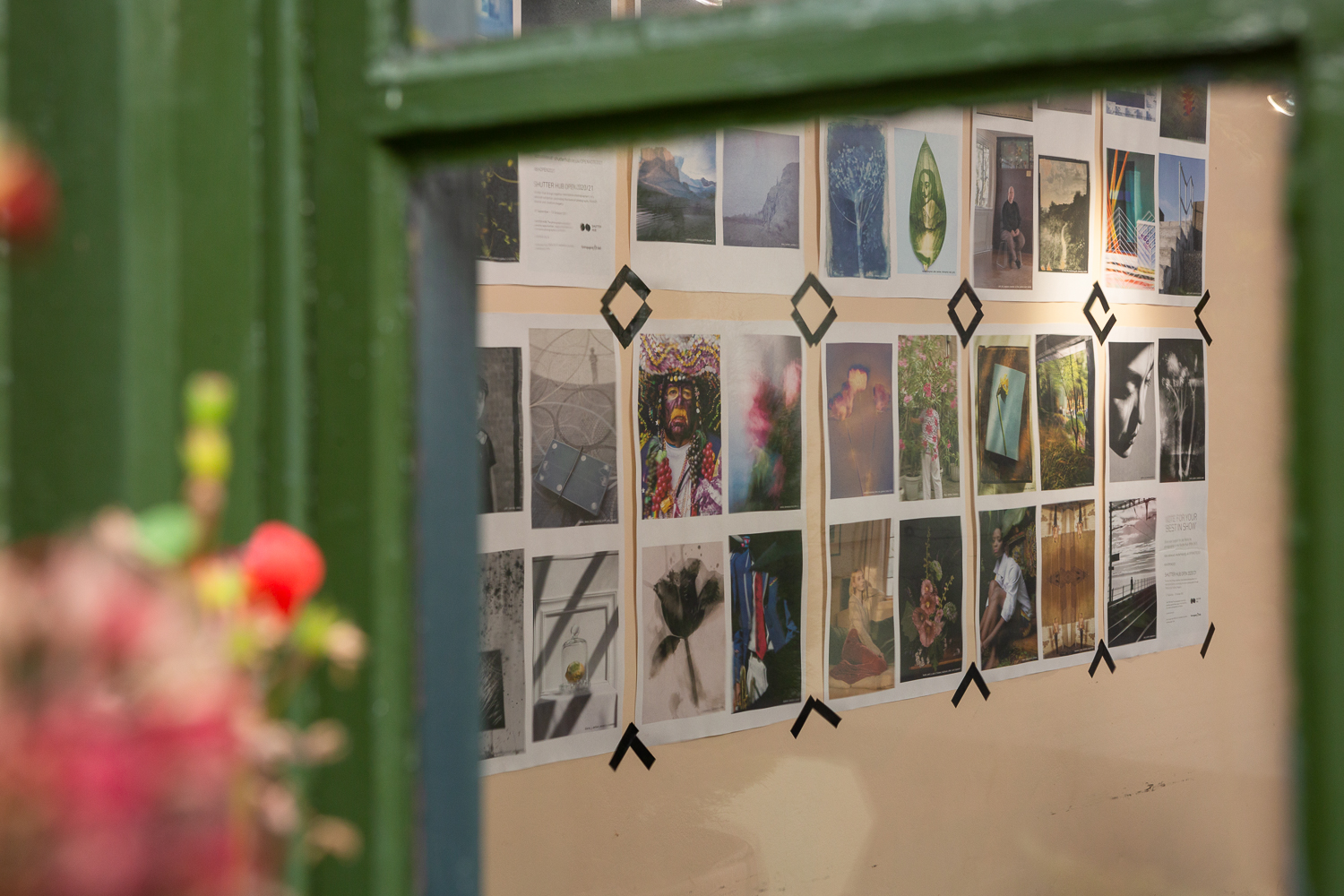 Photograph looking through a window into the Gallery Café at St. Margaret's House, showing an exhibition of photographs printed on newsprint,