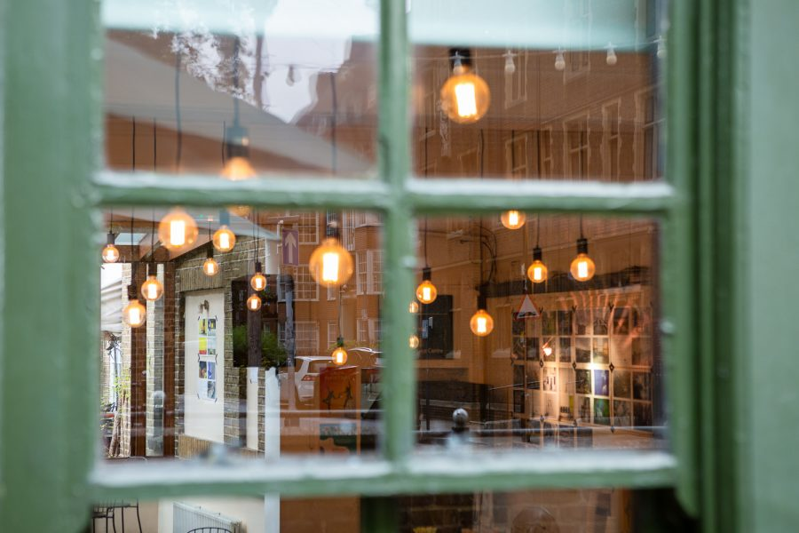 Photograph looking through a window into the Gallery Café at St. Margaret's House, showing an exhibition of photographs printed on newsprint, and light bulbs hanging from the ceiling