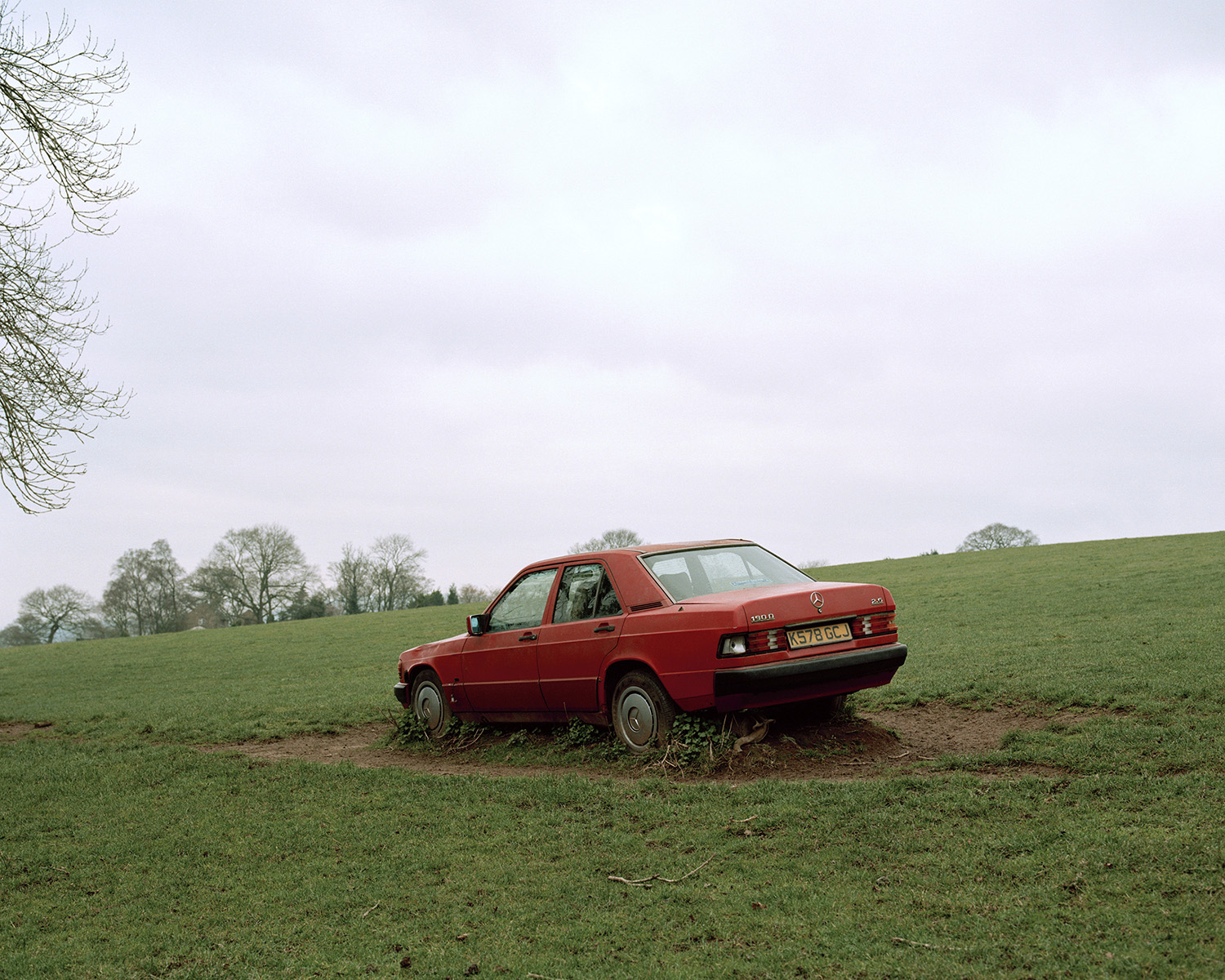 Photograph of an old red Mercedes in a field