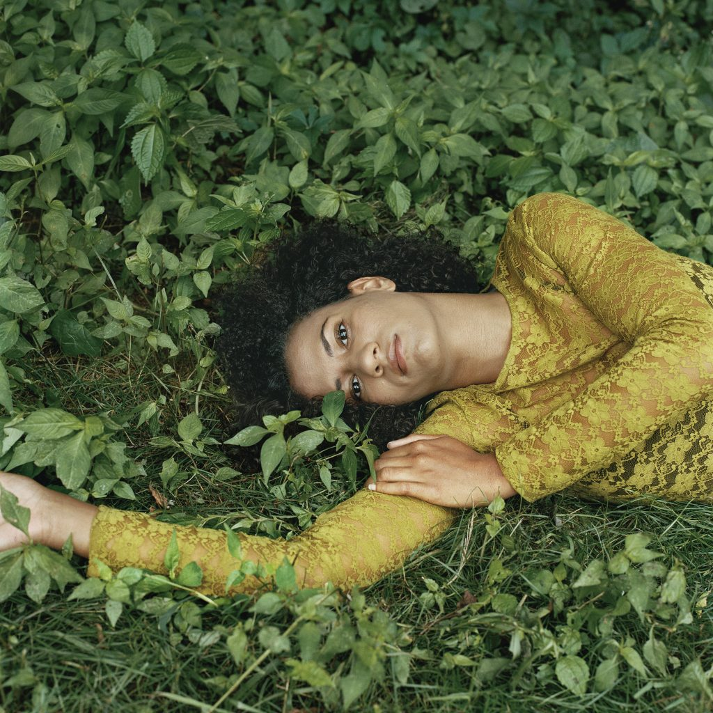 Photographic portrait of reclining women, on green grass, with dark hair and yellow blouse