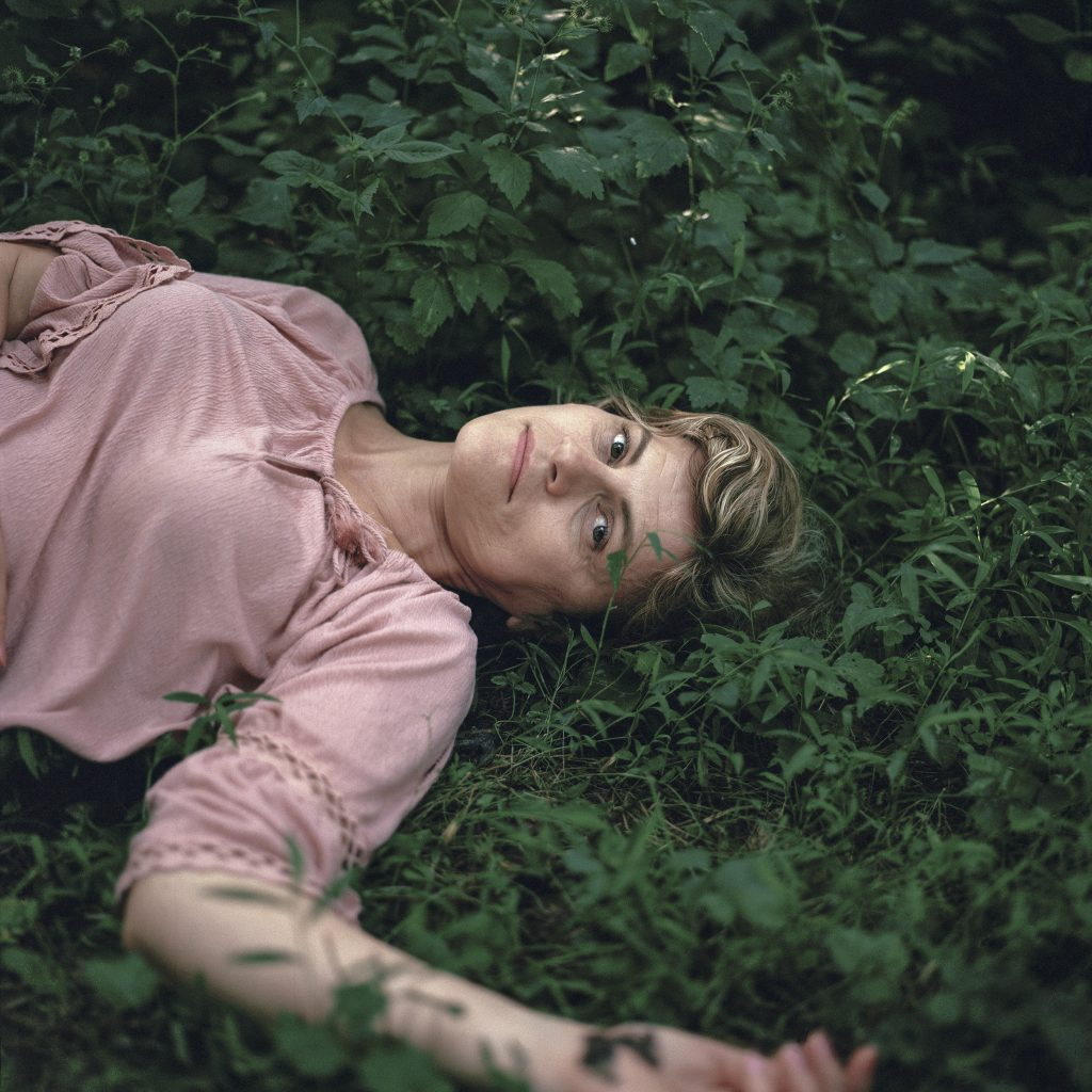 Photographic portrait of reclining women on green grass, with blonde hair and pink blouse