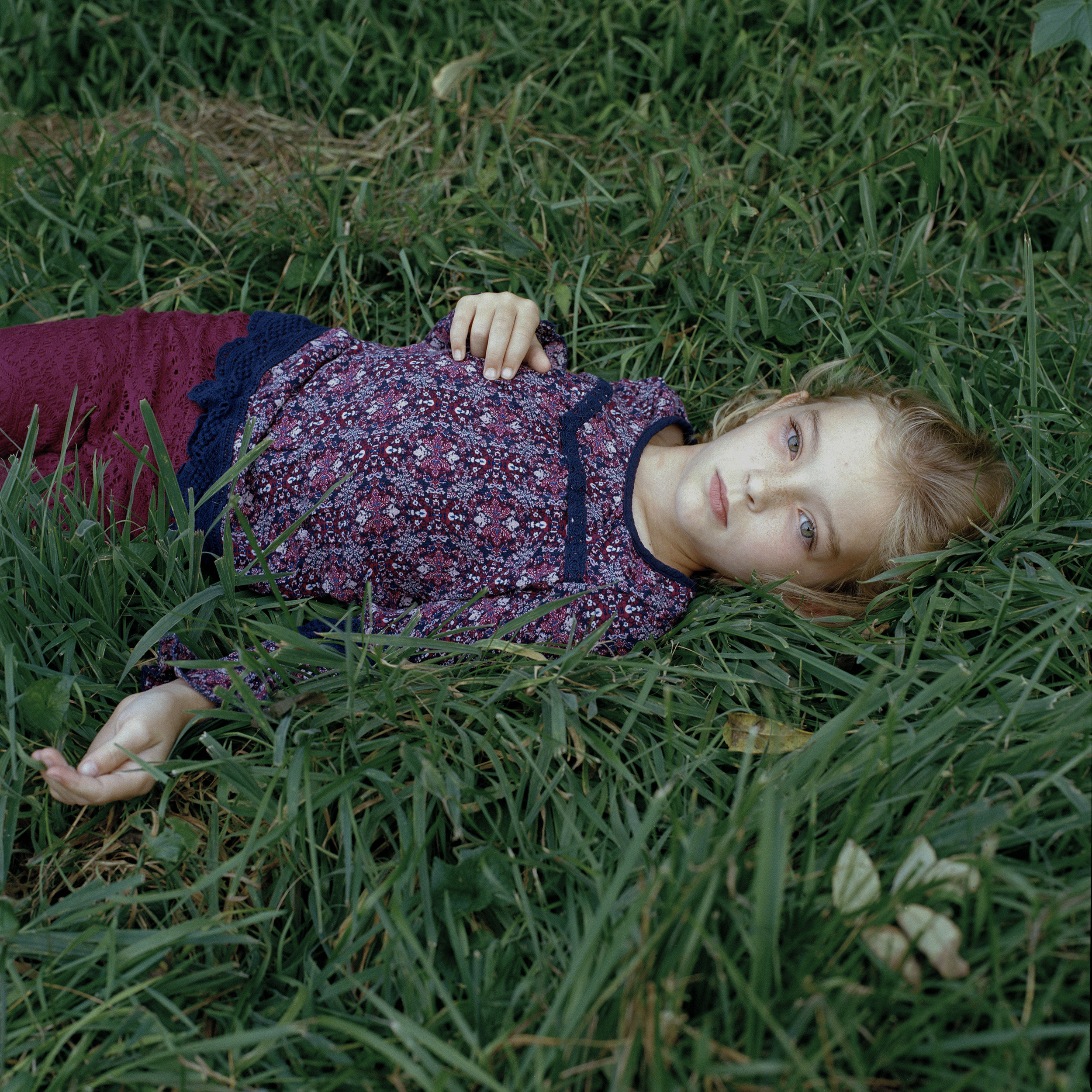 Photographic portrait of reclining girl on green grass, with purple blouse and pants