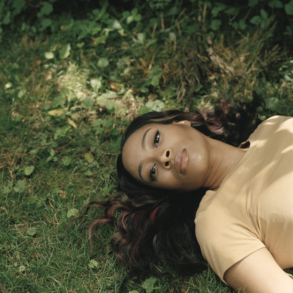 Photographic portrait of reclining women on green grass with dark hair and yellow blouse