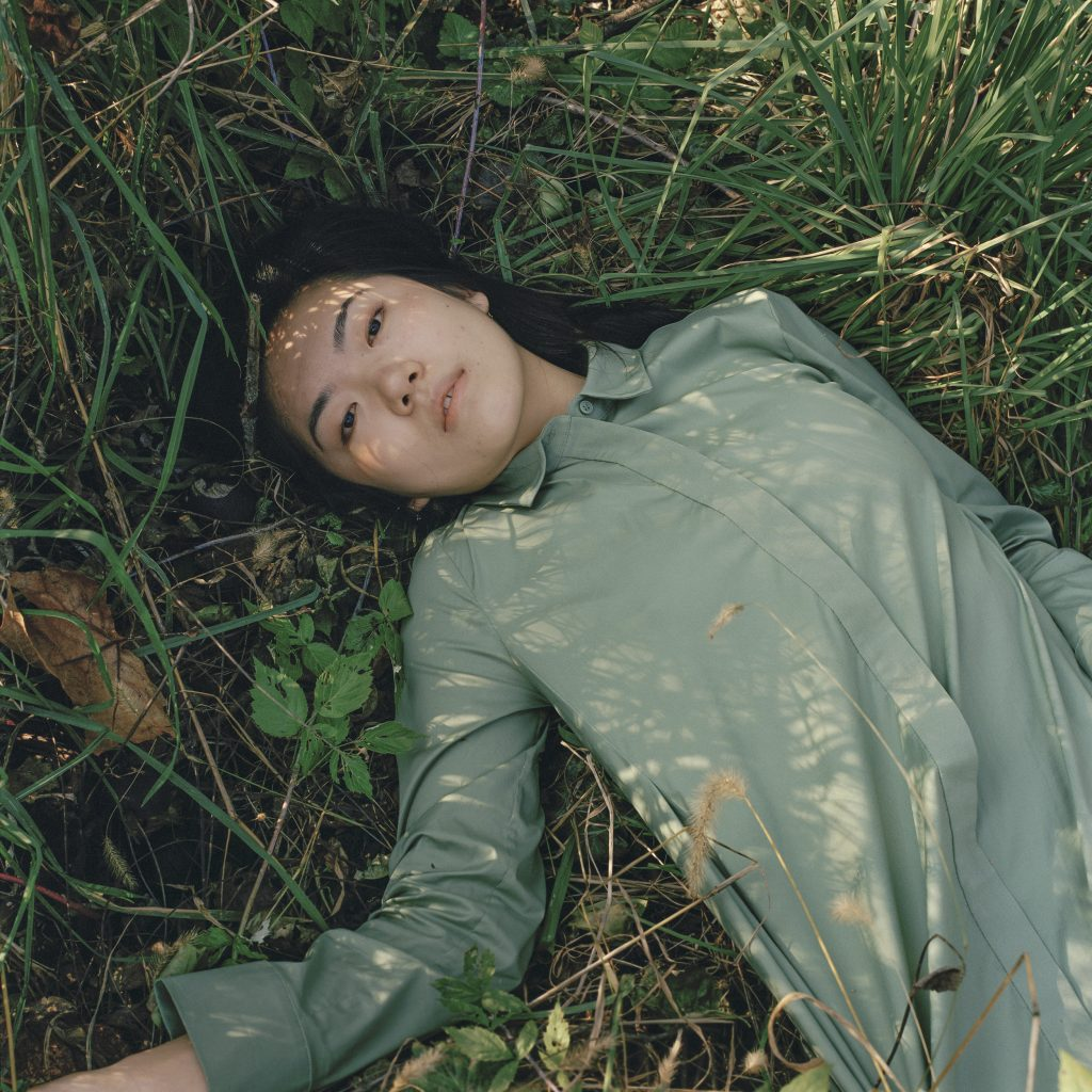 Photographic portrait of reclining woman on green grass, with dark hair and green blouse
