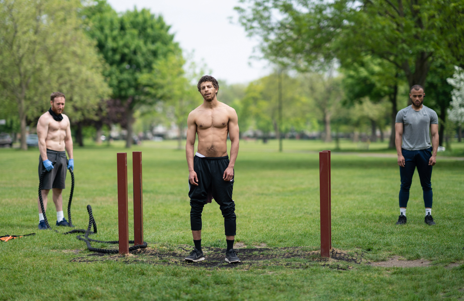 Photograph of 3 men in a park facing the camera mid-exercise regime