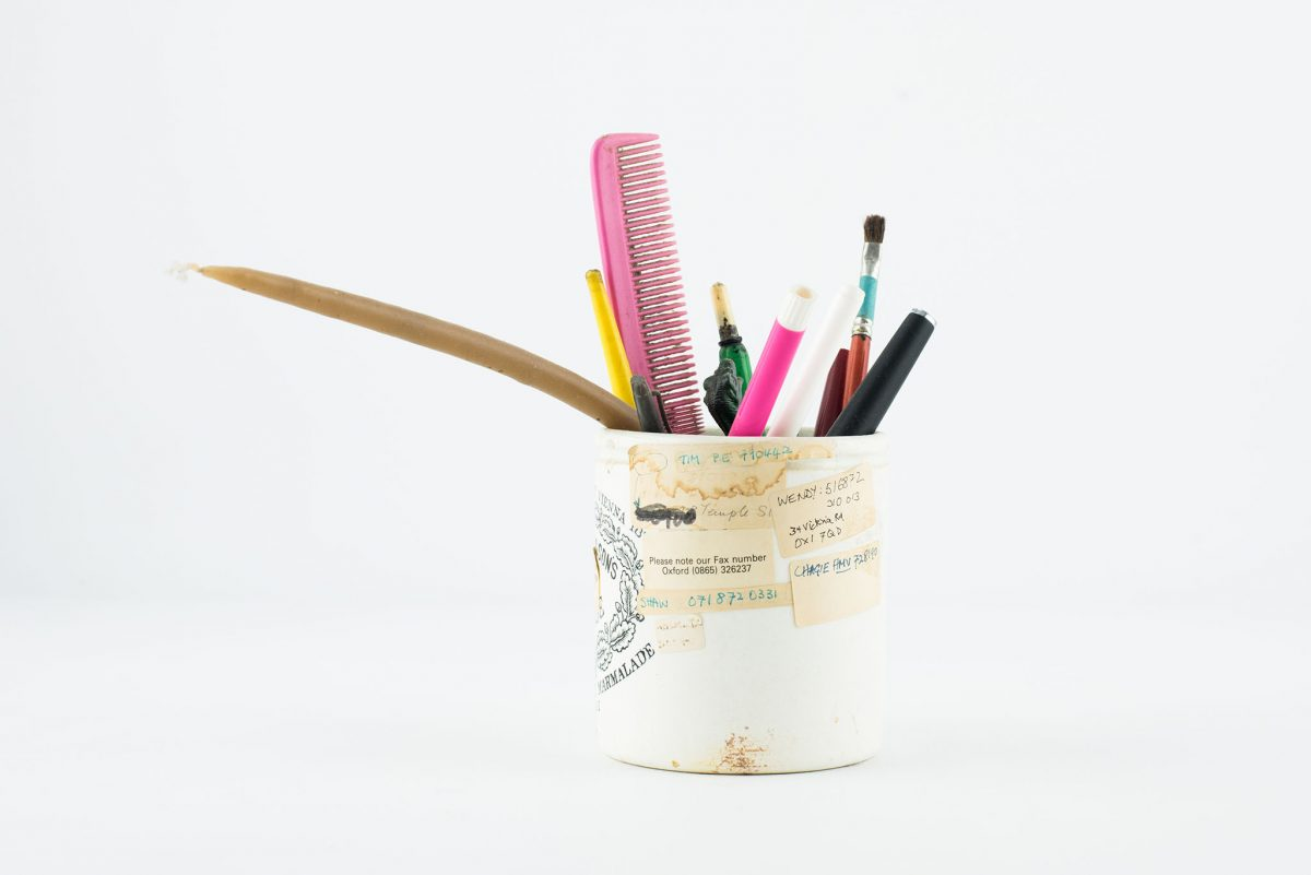 white container filled with pencils, brushes and a pink comb, white background