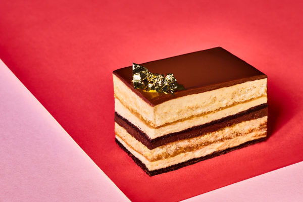 slice of layered cake on pink and red background