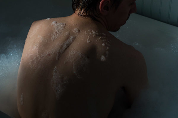 Photograph of a person sitting upright in a bubble bath with their back to the camera, mostly in darkness, with light hitting their left shoulder