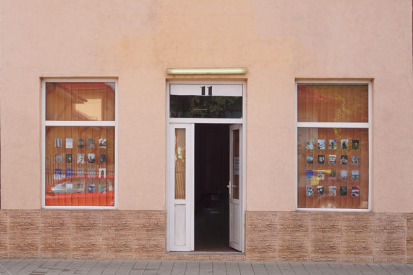 Shutter Hub Postcards from Great Britain in two windows either side of an open door, with a peach facade, Calarasi Romania