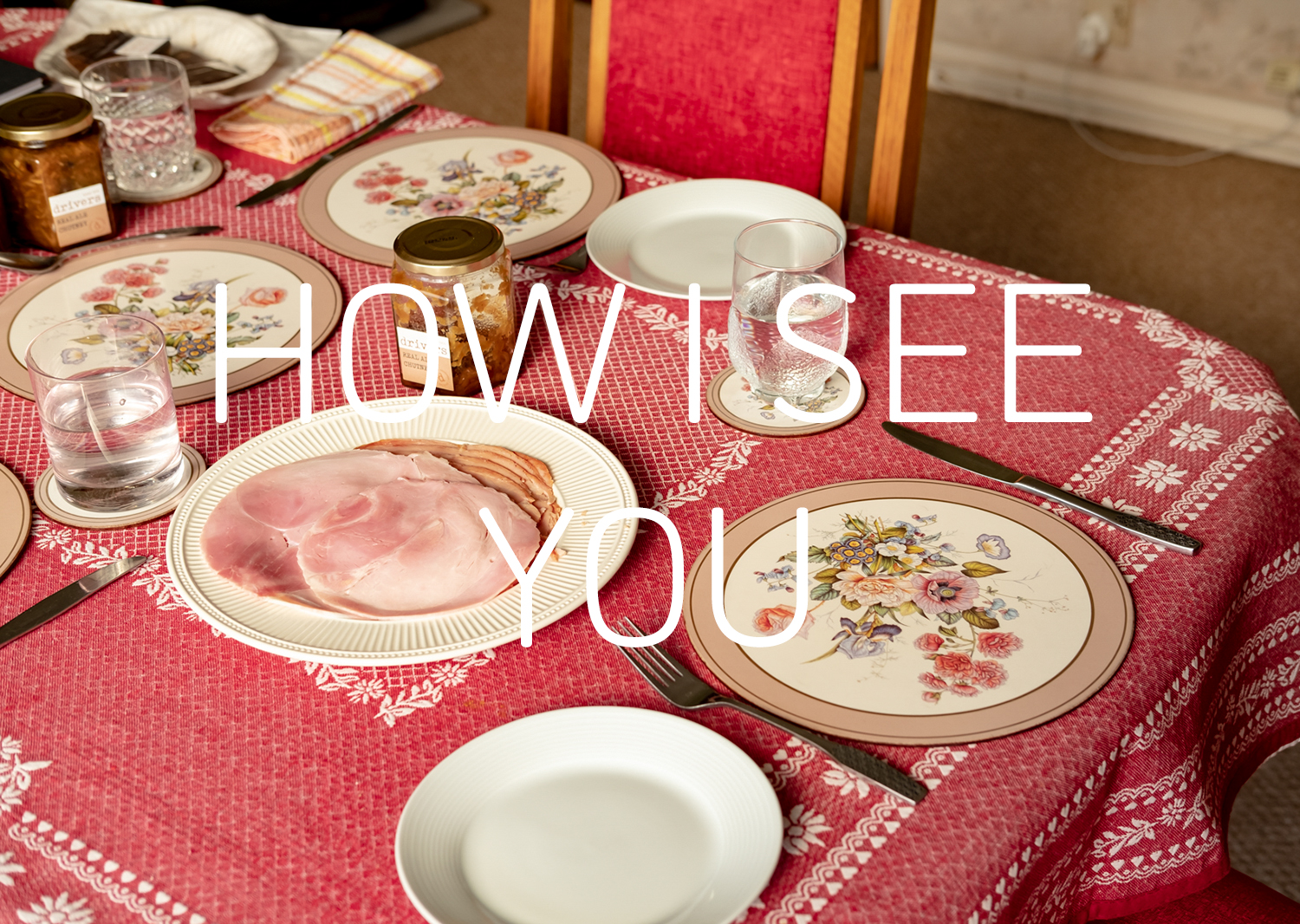 Graphic with a photograph of a table set for lunch with a pink tablecloth, plate of ham, a floral placemat, cutlery, a jar of chutney and glasses of water. Text in white in the middle says 'HOW I SEE YOU'