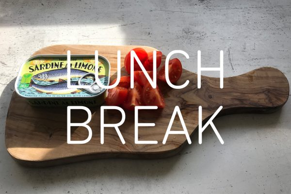 Photograph of a wooden board with a tin of fish and a cut tomato on a gray marble table with the words 'LUNCH BREAK' in white over the centre of the image