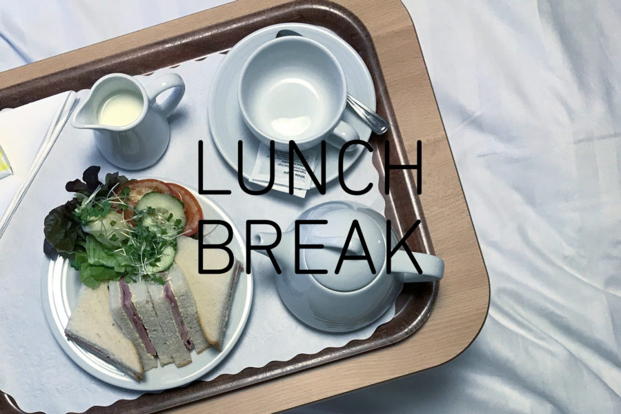 Photograph looking down on a tray with triangular ham sandwiches and a side salad, a small jug of milk, cup and saucer and small teapot, with the words 'LUNCH BREAK' in the centre
