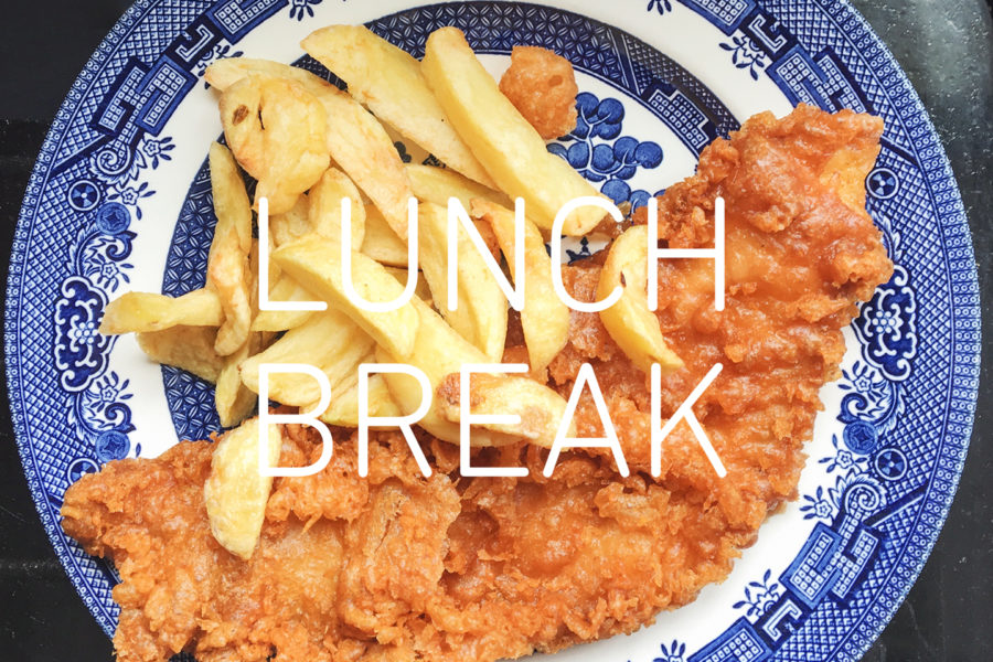 Photograph of a blue and white 'Willow' pattern plate with fish and chips on top, and text reading 'Lunch Break' in white in the centre