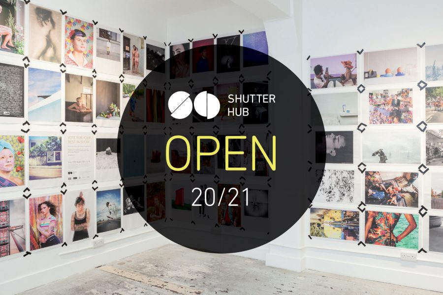 Graphic with a photograph of newspaper poster printed photographs displayed taped to the walls at London's Old Truman Brewery, with a black circle in the centre containing the Shutter Hub logo, with 'OPEN' and '20/21' below.