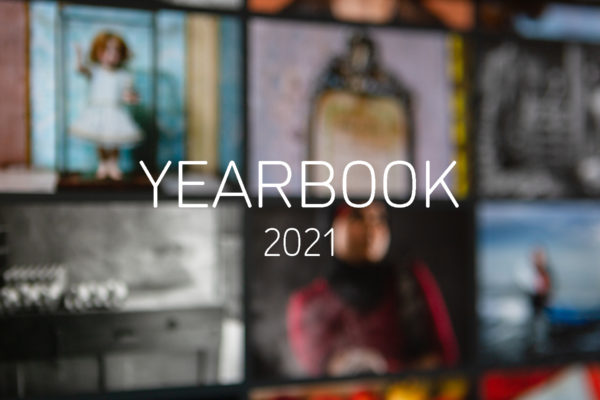 Graphic with an out of focus photograph of a computer monitor displaying the YEARBOOK 2020 online exhibition, with white text in the centre reading'YEARBOOK 2021'