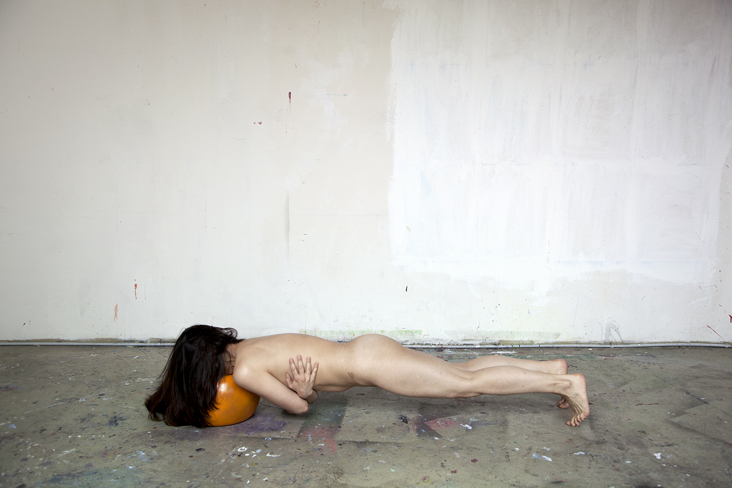 Photograph of a naked person face down on the floor in a plank position with their dark hair covering the orange object upon which their face is resting.