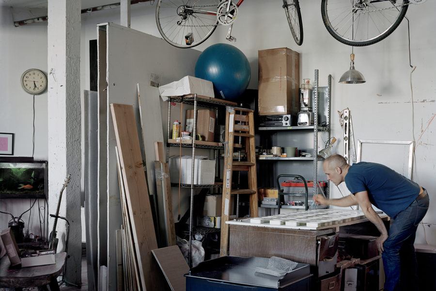 A man makes soaps with street-found objects enclosed in glycerin in his open-space living room repurposed as a workshop.