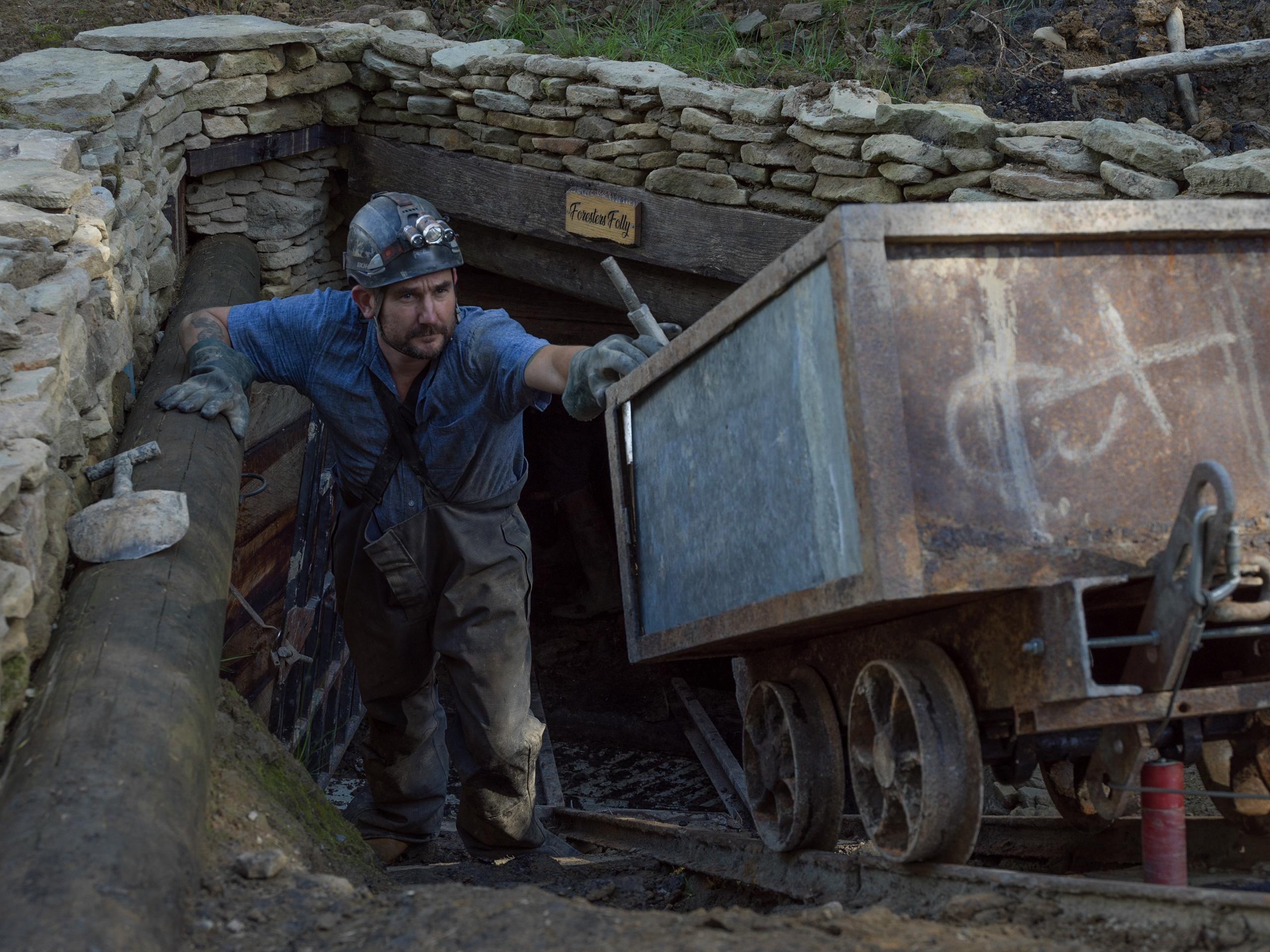 Miner exiting mine entrance