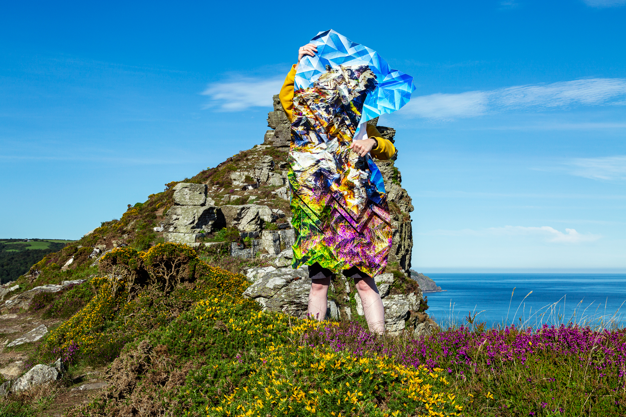 Image of a woman standing on a cliff top and holding a large, intricately-folded, photograph that blends in with the landscape.