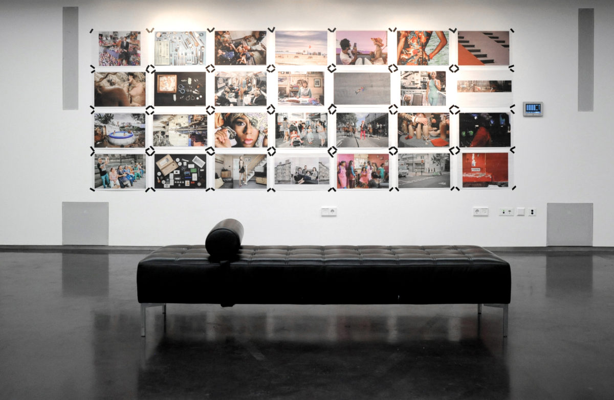Photograph of an exhibition with newsprint poster photographs taped to the wall, with a long black seat in front